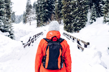 Woman in winter warm jacket and gray woolen hat with backpack walking in snowy winter forest