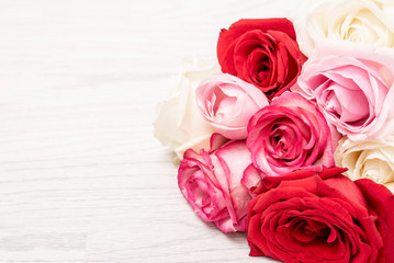 Frame made from pink, red, white roses on vintage white wooden background effect. Flat lay, top view.
