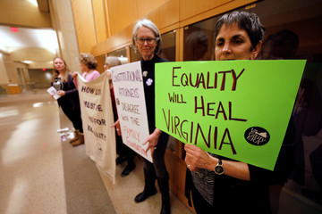 Women's rights activists demonstrate with placards in the halls of the state capitol in Richmond