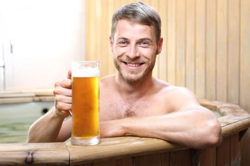 Obraz Męskie spa. Przystojny mężczyzna zażywa kąpieli w bali z woda termalną pijąc piwo kuflowe. - fototapety do salonu
