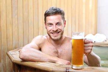 Obraz Męski relaks.   Przystojny mężczyzna zażywa kąpieli w bali z woda termalną pijąc piwo kuflowe. - fototapety do salonu