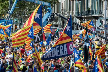 People wave 'Esteladas' (pro-independence Catalan flags) as they gather during a pro-independence demonstration, on September 11, 2017 in Barcelona during the National Day of Catalonia, the 'Diada'.