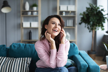 Happy cheerful young woman talking on the phone sitting on comfortable couch at home.