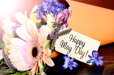 Happy May Day traditional gift of Spring Flowers in orange paper cone on dark wood table with lens flare.