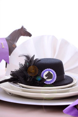 Horse racing Ladies Luncheon fine dining table setting with small black fascinator hat, decorations and champagne, with lens flare.
