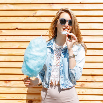 Positive happy young hipster woman in black sunglasses in a stylish denim jacket in a lace blouse in a skirt smiles and eats cotton candy near a wooden wall on a sunny warm day. Cheerful girl.