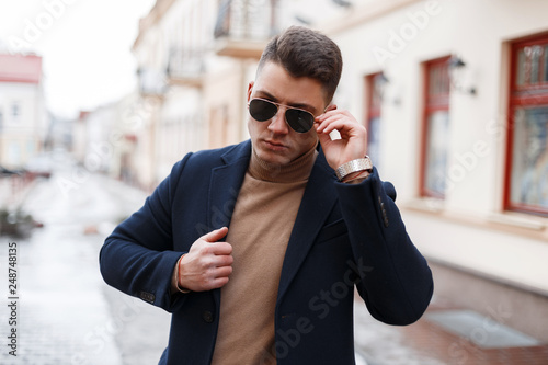 766f6ffa135 Handsome stylish young hipster man with a stylish hairstyle in a black coat  in trendy sunglasses in a vintage knitted sweater with a backpack poses in  the ...