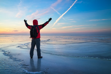 Nature photographer traveler on the frozen lake during sunrise in winter. Beautiful colorful landscape with people