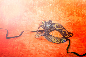 Mardi Gras mask on a bright, colorful orange background, closeup with lens flare.