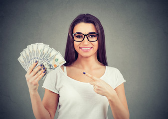Portrait of a happy woman in casual clothing holding fan of money
