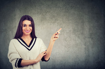 woman wearing white pullover expressing happiness pointing finger aside