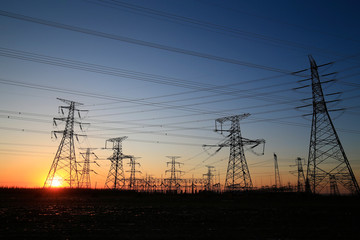 A high-voltage tower in the setting sun against the sky