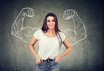 Strong happy young woman flexing her muscles
