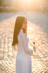 Vietnamese girl dressed Ao Dai white dress. Vietnamese traditional dress. View from back.