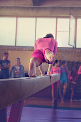 Young girl athlete gymnast on balance beam competition in gymnastics. Focus on feet - Image