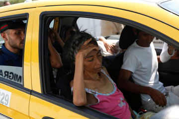 A sick woman takes a taxi with her family on the Francisco de Paula Santander international bridge in Cucuta