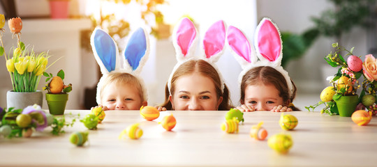 Happy easter! family mother and children with ears hare getting ready for holiday.