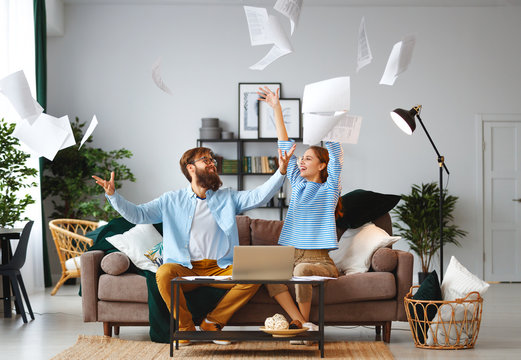 married couple with bills receipts documents and laptop at home.