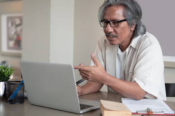 Senior Asian man at home connected on laptop computer.