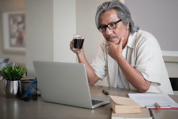 Senior Asian man working at home connected on laptop computer. education or technology or startup business after retirement concept with copy space