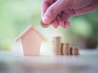 Hand putting money coins with home model on nature green background. Finance and house loan, refinance, Property Investment and business, credit concept. with copy space