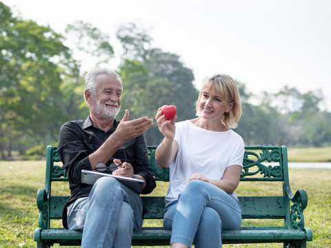 Senior man and woman couple give a heart in a park on a sunny day. Valentine's Day, Health, lifestyle, care, retirement grandparents concept.