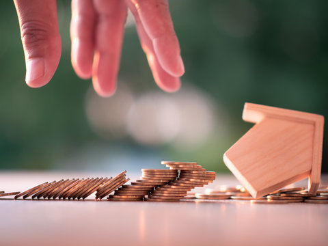 Money coins stacks with model house falling on nature green background and sunlight. Finance and house loan, refinance, Property Investment and business, bankruptcy, credit concept. with copy space