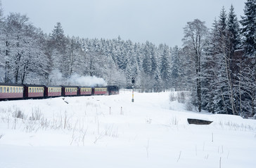 Old steam train near the german Harz mountains driving through a valley covered in snow