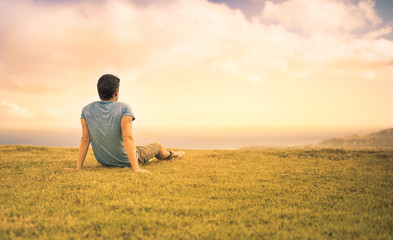 Young man sitting in a field watching the sunset