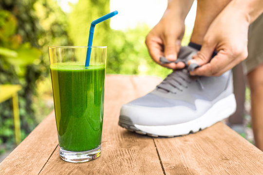Green smoothie. Man tying shoe next to healthy drink.