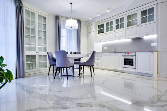 Minimalistic interior of living room in light tone with marble flooring, large windows and a table for four persons