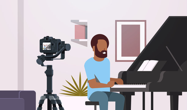 guy musical blogger recording video on camera african american man playing classical piano music blog concept modern apartment interior closeup portrait horizontal