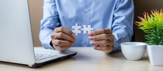 Businessman Hand connecting couple puzzle piece in office. Business solutions, mission, successful, goals and strategy concepts