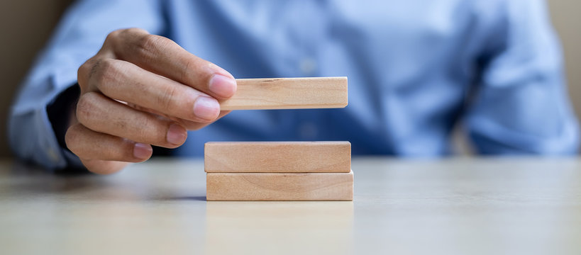 Businessman hand holding wooden building blocks on table background. Business planning, Risk Management, Solution and strategy Concepts