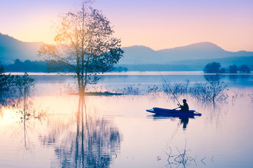 Sunrise in morning on lake with tree and silhouette fisherman boat, Surrounded by mountains background - image