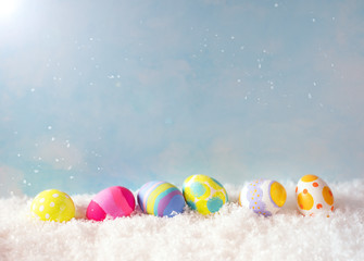 Colorful Happy Easter Eggs in Snow against Blue Sky with sunlight with room or space for copy, text, or your words.  Horizontal with side view