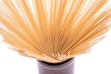 Organic uncooked Brown Rice Spaghetti pasta arranged in a tall round brown ceramic jar isolated on white background. Gluten-free and sodium-free  alternative to traditional pastas.