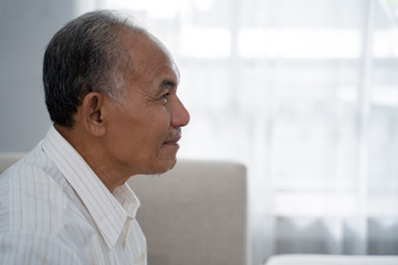 closeup from side view of Asian old man sitting on the sofa a background of window with curtain