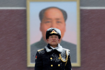 Paramilitary officer stands guard in front of a portrait of the late Chinese Chairman Mao Zedong amid snow at the Tiananmen Square in Beijing