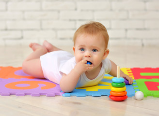 A 7-month-old baby plays on the floor with toys and stuffs small parts into his mouth. Security concept