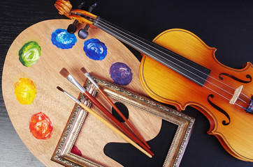 Violin, art palette, brushes, picture frame on a black background