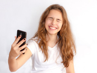 Pretty teenager girl with long hair makes selfie with funny laughing face