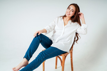 Beauty fashion portrait of smiling sensual asian young woman with dark long hair in white shirt sitting on chair on white background Wall mural