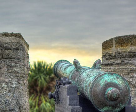 An aqua blue Spanish colonial cannon on top of an old Spanish fort, overseeing a cloudy dusky sky and palm trees. Shot in Castillo de San Marcos, St Augustine, Florida, USA.