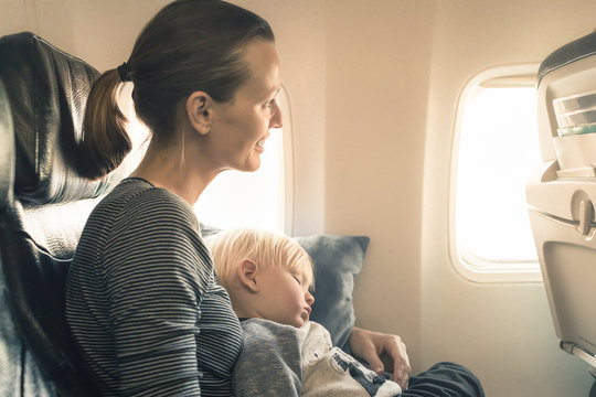 Happy mother traveling on airplane with her baby boy.