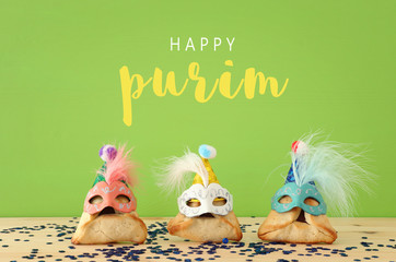 Purim celebration concept (jewish carnival holiday). Traditional hamantaschen cookies with cute clown hats and masks over wooden table and green background.