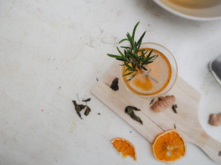 Glass with citrus, genger and rosemary flavored kombucha tea on a white background