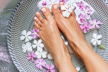 Spa treatment and product for woman feet and foot spa. Foot bath in bowl with tropical flowers, Thailand. Healthy Concept. Closeup  of  beautiful female feet, legs at spa salon on pedicure procedure.
