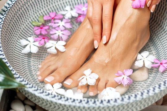 Spa treatment and product for female feet and foot spa. Foot bath in bowl with tropical flowers, Thailand. Healthy Concept. Beautiful female feet, legs at spa salon on pedicure procedure.