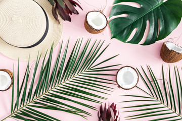 Summer composition. Tropical palm leaves, hat, coconut on pastel pink background. Summer concept. Flat lay, top view